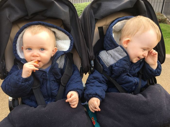 Cute baby boys sitting in baby carriages