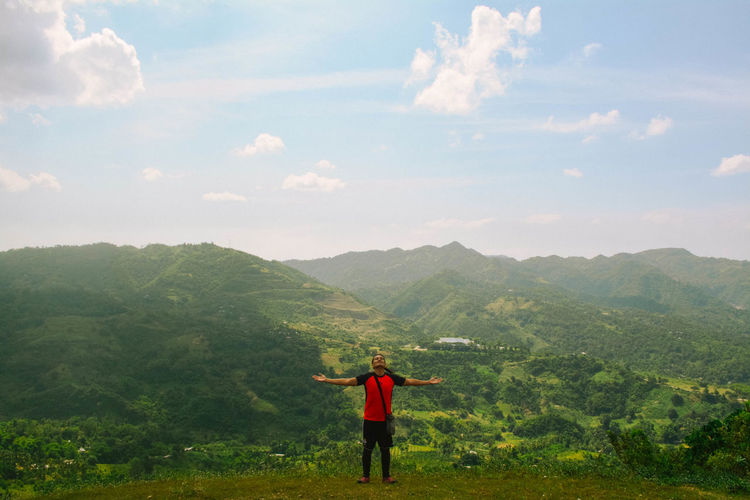 Man standing on grass against mountains and sky