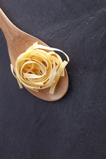 fettuccine pasta on the black slate Black Background Copy Space Dried Food Food And Drink Freshness Spaghetti Black Background Close-up Directly Above Fettuccine Food Healthy Eating High Angle View Indoors  Ingredient Italian Food Kitchen Utensil No People Pasta Raw Food Spaghetti Still Life Studio Shot Wellbeing Wooden Spoon