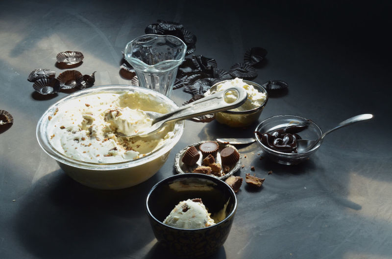 Ice cream in bowls with peanut butter cupcakes and chocolates on table