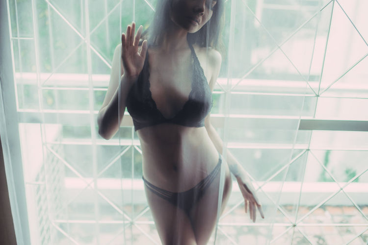 Sensuous young woman in lingerie seen through curtain at home