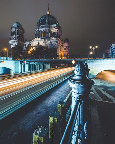 Light trails on road by berlin cathedral against sky at night