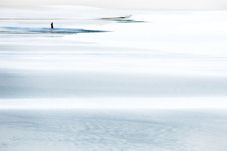 Distant view of man standing at frozen beach