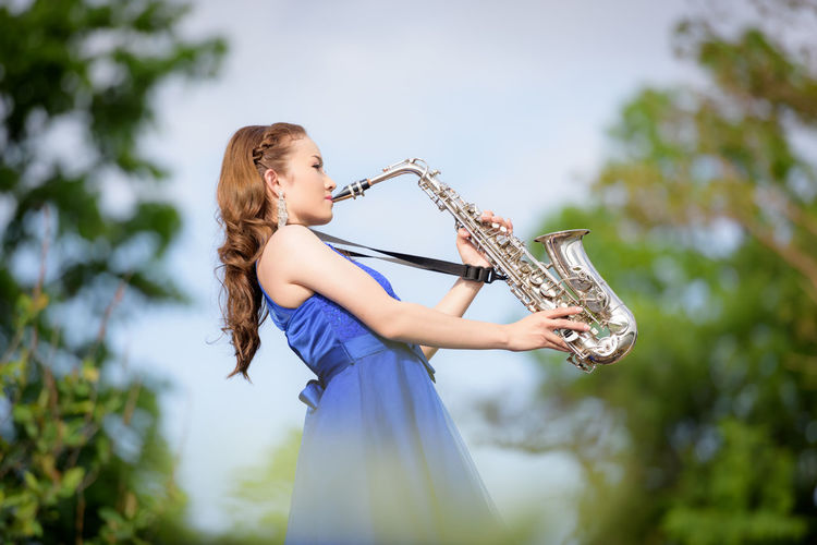 Side View Of Young Bride Playing Saxophone In Park