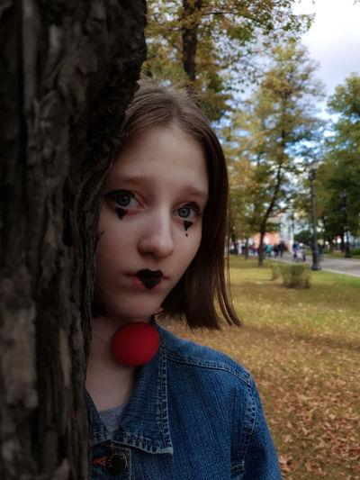 Portrait of teenage girl against tree trunk
