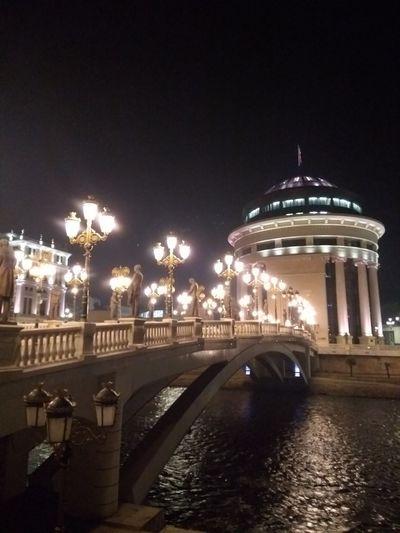 Illuminated arch bridge over river against sky at night