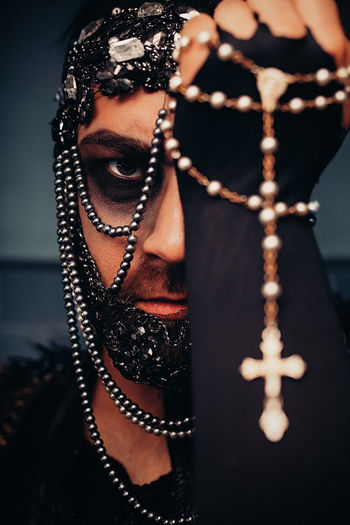 Close-up portrait of serious man in costume holding rosary