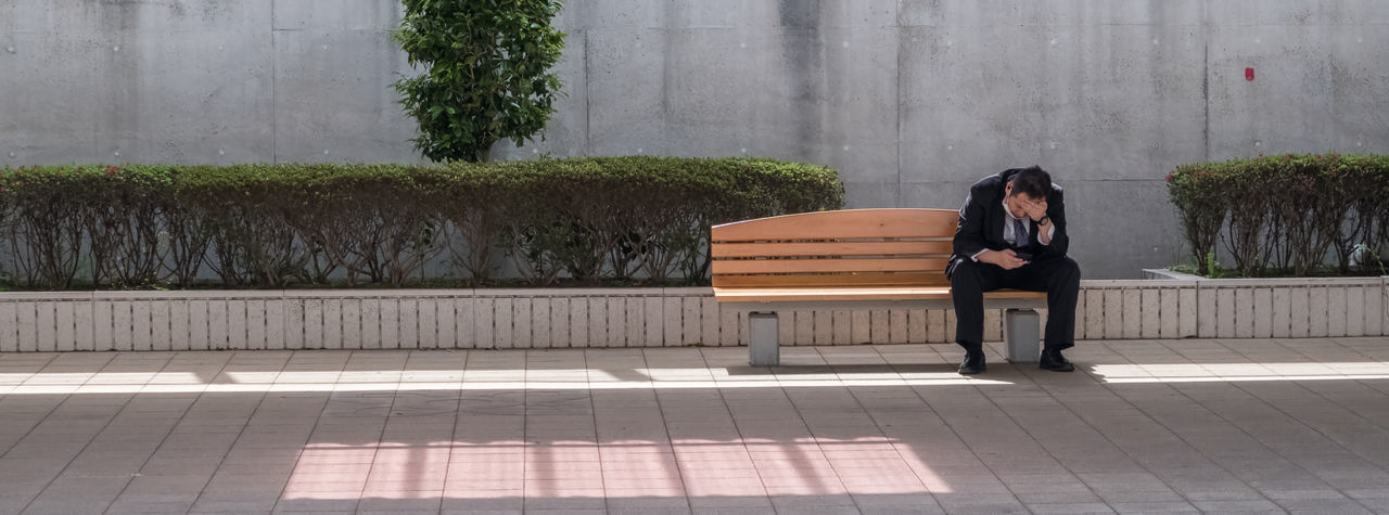 Woman sitting on bench against plants