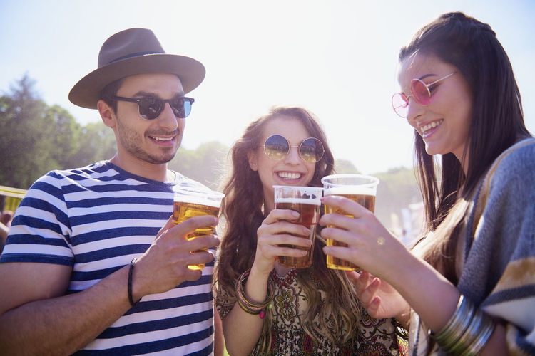 Man and women holding drink in glasses against sky