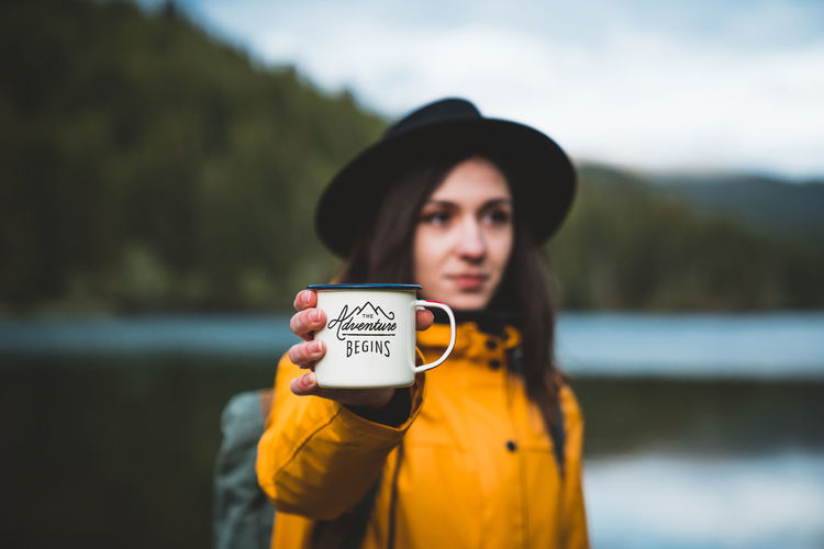 Portrait of woman standing against lake