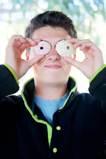 Close-up of young man holding seashells in front on eyes