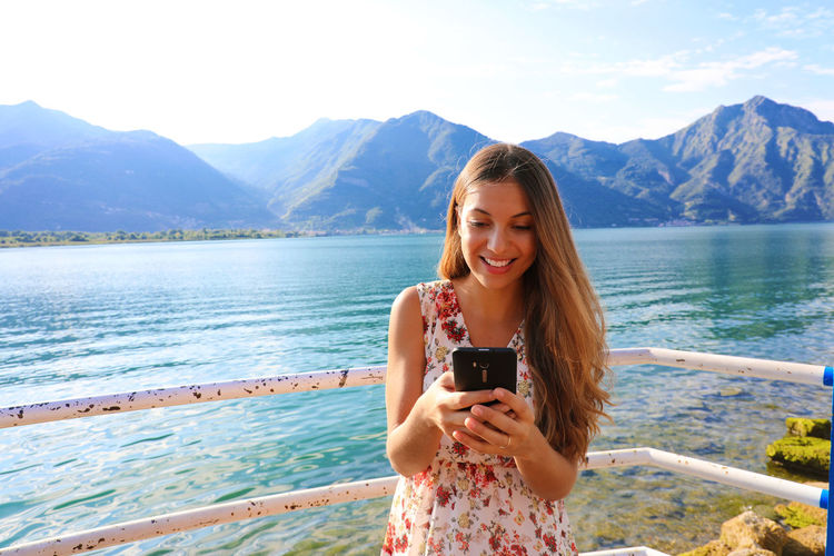 Smiling Young Woman Using Mobile Phone Against River
