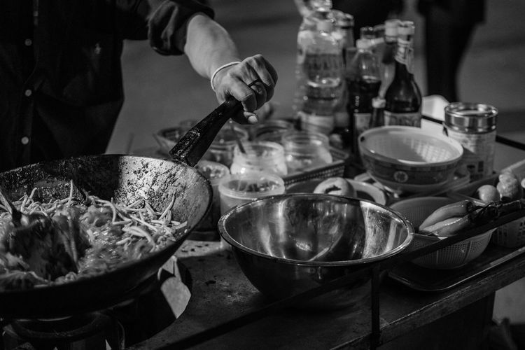 Midsection of man preparing noodles in wok