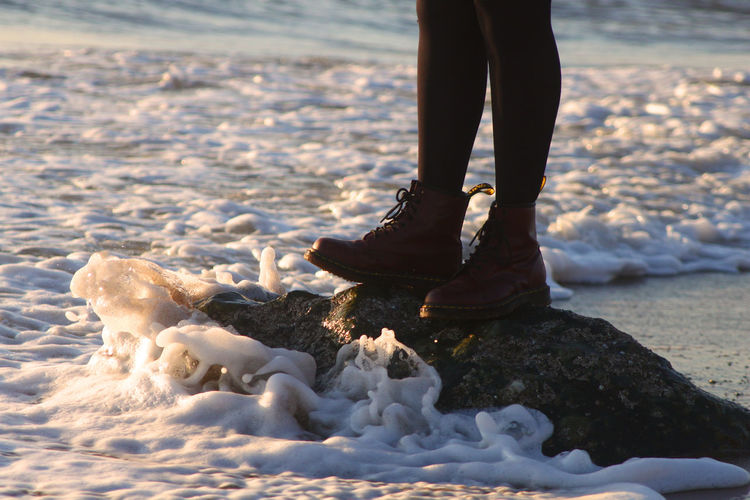 Standing on a rock on the beach. Boots Calm EyeEm Best Shots EyeEm Nature Lover EyeEm Gallery EyeEmNewHere Fashion Animal Themes Beach Cold Temperature Day Human Leg Low Section Nature One Person Outdoors People Pets Real People Sand Sea Standing Tourism Water Winter