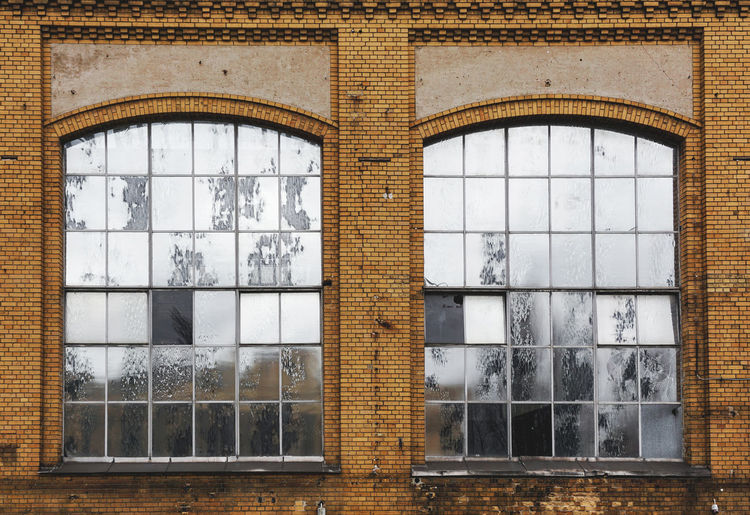 old industrial building Window Glass - Material Architecture Transparent Built Structure Reflection No People Building Building Exterior Day Outdoors Glass Tree Sky Geometric Shape Wall Shape Arch Window Frame Industrial Reflections Old Abandoned Industry