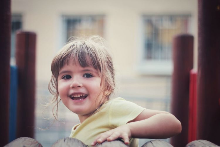 Portrait Of Cute Cheerful Girl Playing At Playground
