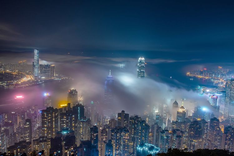 High Angle View Of Illuminated Buildings In City At Night During Foggy Weather
