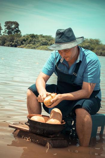 Man wearing hat sitting in water