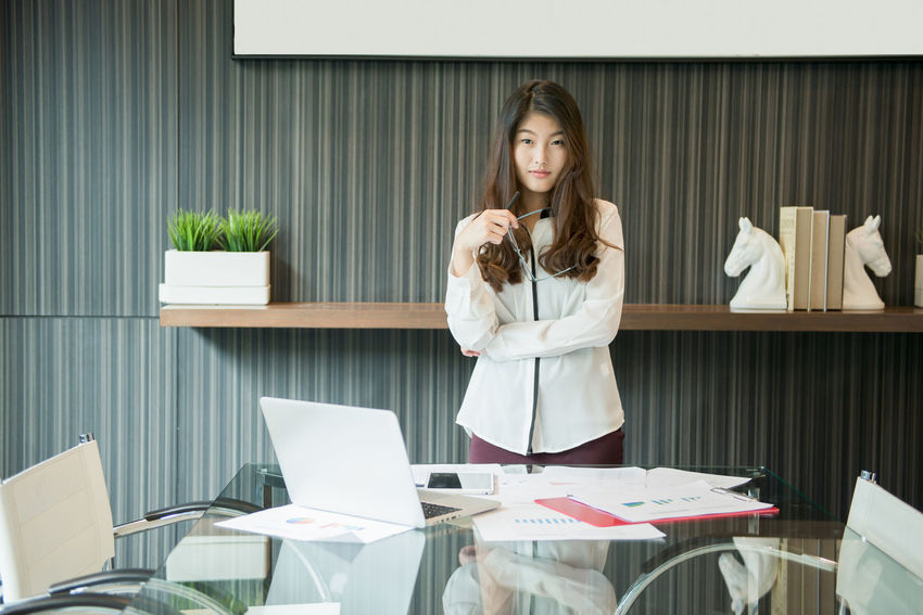 An Asian business woman presenting in meeting room Office Working Adult Business Business Woman Day Fashion Holding Indoors  Laptop Meeting Room Occupation One Person People Real People Standing Table Well-dressed Women Working Young Adult Young Women