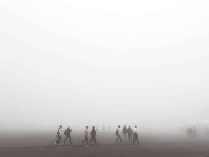 Silhouette people on field against sky during foggy weather