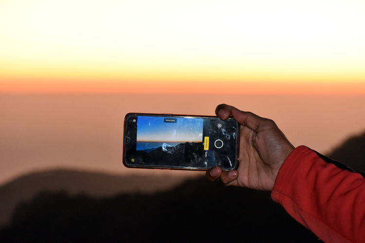 Man photographing on mobile phone at sunset