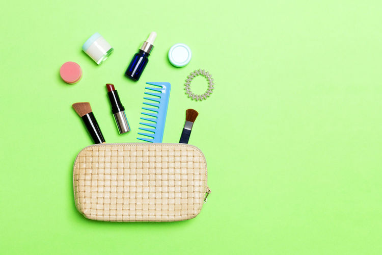 Directly above shot of purse with beauty products over green background
