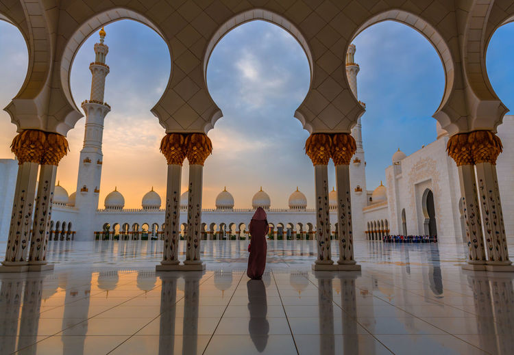 Woman in traditional Arabic abaya robes stands with her back facing the camera as she stands under tall archways and looks toward the setting sun behind the main domes and tower. Photo inside the Sheikh Zayed Grand Mosque in Abu Dhabi Abu Dhabi Back Cloudscape Grand Mosque Abu Dhabi Jedi Sheikh Zayed Grand Mosque Silhouette Sunset Silhouettes Sunset_collection Tourist Tourist Attraction  Woman Abaya Dome Grand Mosque Islam Landmark Muslim Religious  Religious Architecture Sunset Sunset #sun #clouds #skylovers #sky #nature #beautifulinnature #naturalbeauty #photography #landscape Tourism Tourist Destination Tower