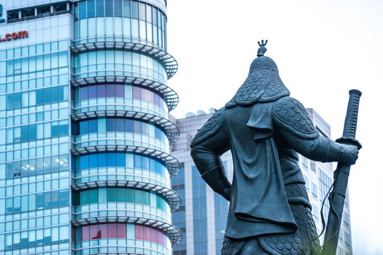 Low angle view of statue against modern buildings