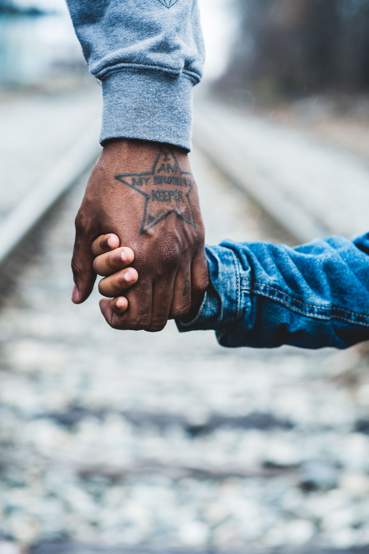 Cropped image of father and son holding hands on railroad track