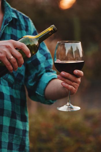 testing a glass of red wine at sunset Refreshment Holding Food And Drink Alcohol Drink Glass Wine Human Body Part Red Wine Human Hand Focus On Foreground Hand Wineglass One Person Real People Food Women Close-up Drinking Glass Drinking