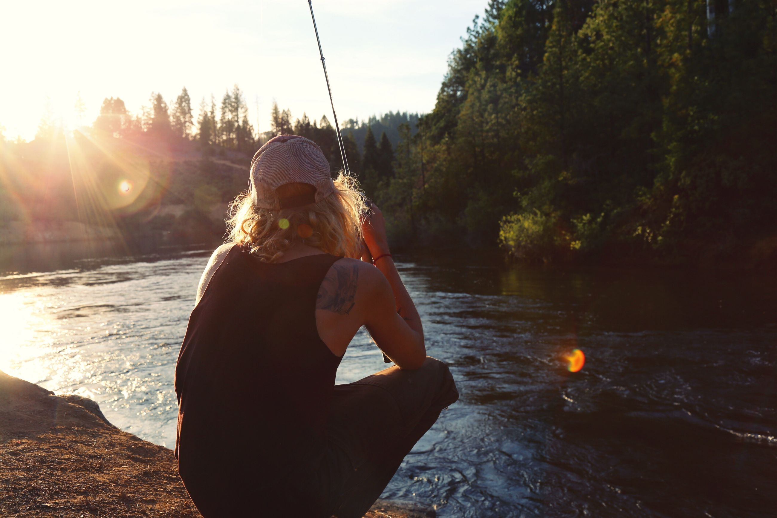 lifestyles, sun, leisure activity, sunlight, sunbeam, water, lens flare, holding, tree, young adult, casual clothing, standing, sunset, sky, river, full length, outdoors, clear sky