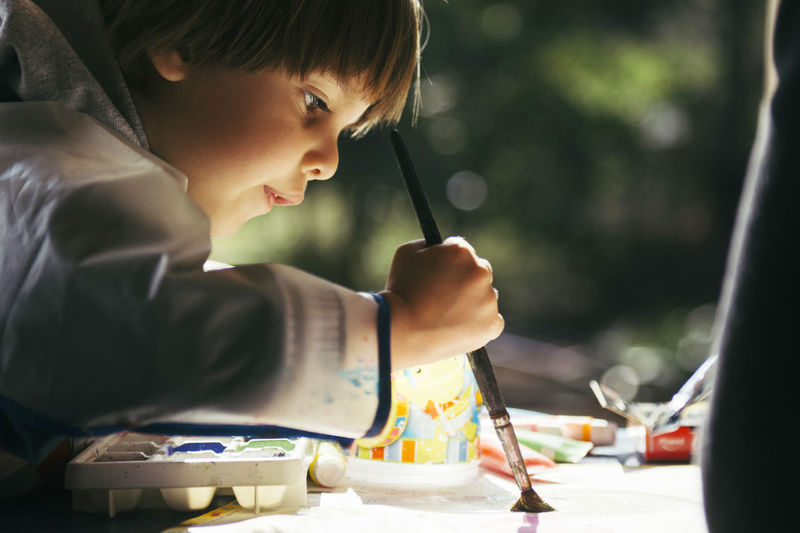 Side view of boy painting