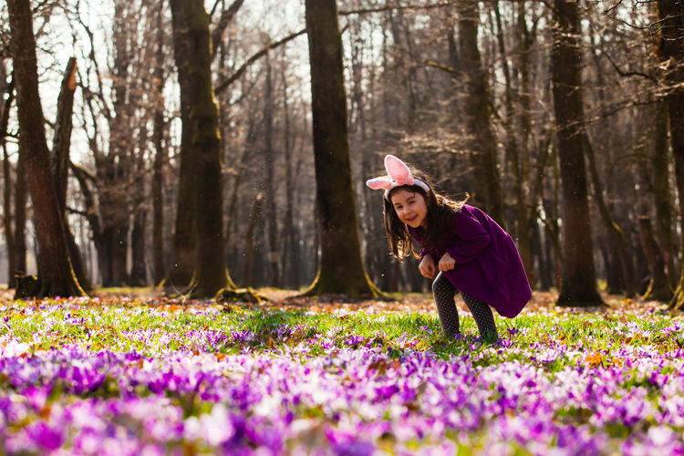 Woman with pink flowers on field by trees in forest