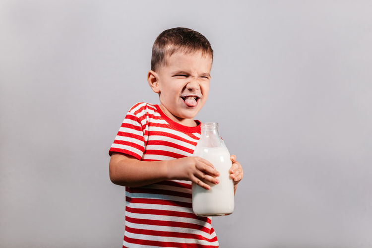 Child with bottle of milk against grey background. Portrait of young boy with milk mustache making faces isolated over gray background - studio shot. Child Striped One Person Drink Drinking Boy Milk Bottle Red Color T-shirt 3-5 Years Grey Gray Background Isolated Studio Shot Indoor Caucasian Horizontal Helth Healthy Eating Dairy Portrait Moustache Mustache