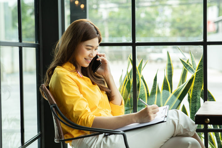 Smiling businesswoman writing on clipboard while talking on mobile phone at office