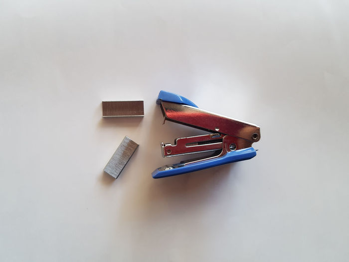 High angle view of stapler and pins over white background