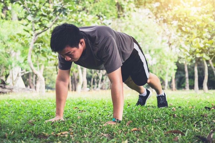 Athlete Bending Casual Clothing Day Effort Excercise Exercising Full Length Gardening Grass Green Color Growth Leisure Activity Lifestyles Men Nature One Person Outdoors Plant Real People Shorts Sport Tree Young Adult Young Men