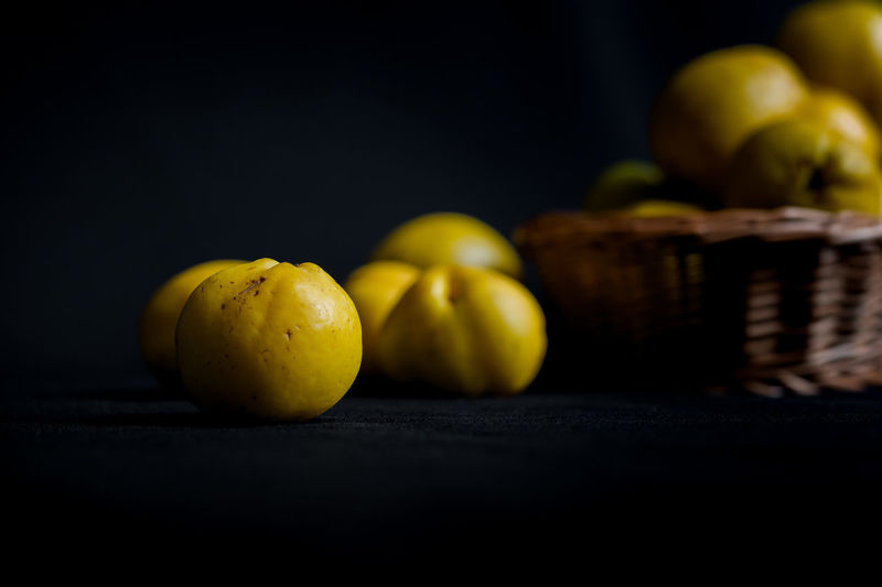 Ripped yellow fruits of quince (Chaenomeles) on dark background table and in woven basket in muted daylight. Close up detailed shot with selective focus and shallow depth of field Autumn Knife Autumn Fruits Black Background Close Up Details Fall Food Food And Drink Freshness Fruit Hand Picked Harvest Healthy Eating Home Grown Fruits Liquer Ingredients Muted Colors Organic Quince Season Fruits Still Life Tea Time Vitamin C Woven Basket Yellow