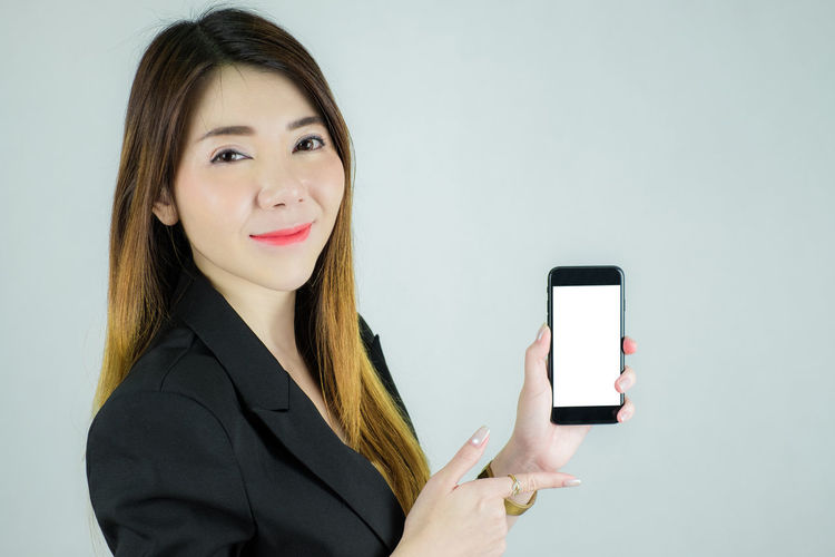 Portrait of a smiling young woman using smart phone against white background