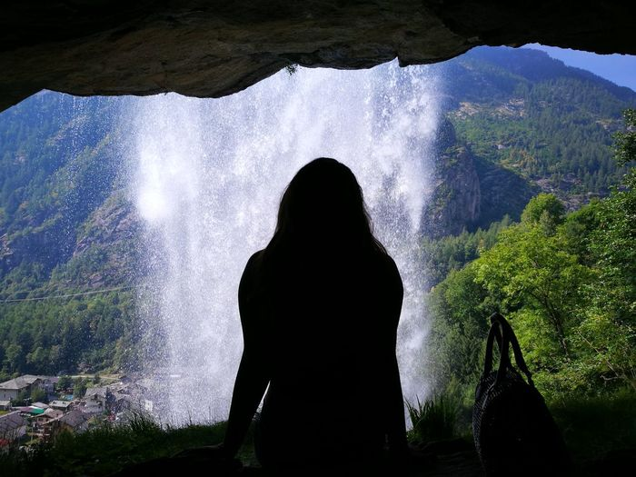 Rear View Of Silhouette Woman Standing Against Waterfall