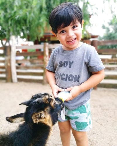 Portrait of cute boy feeding milk to goat
