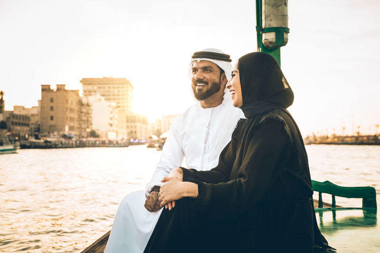 Cheerful couple talking while sitting in boat on river in city