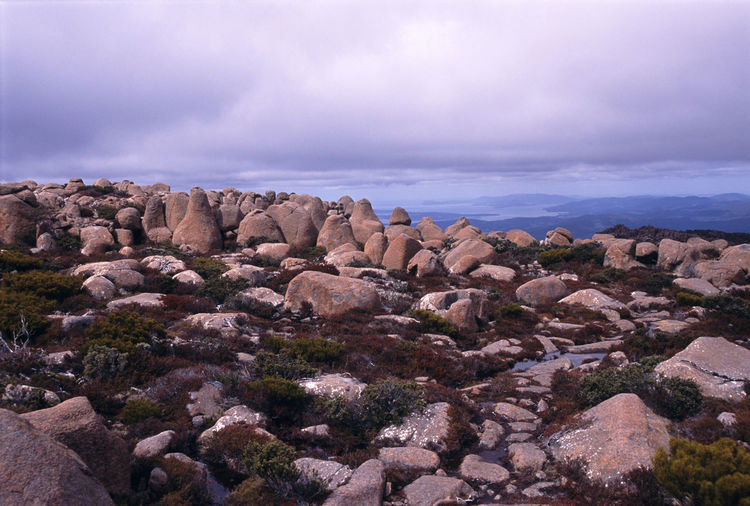 Rocks on mountains against cloudy sky