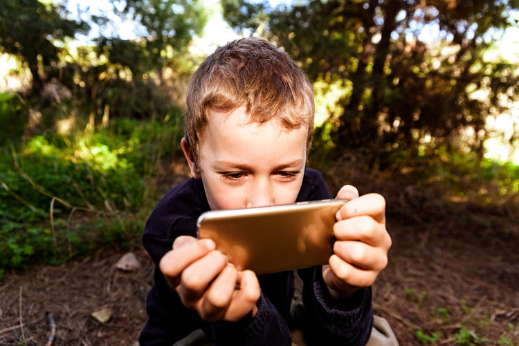 Boy holding mobile phone while sitting outdoors