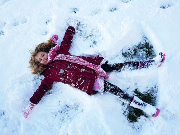 High angle view of girl lying down on snow