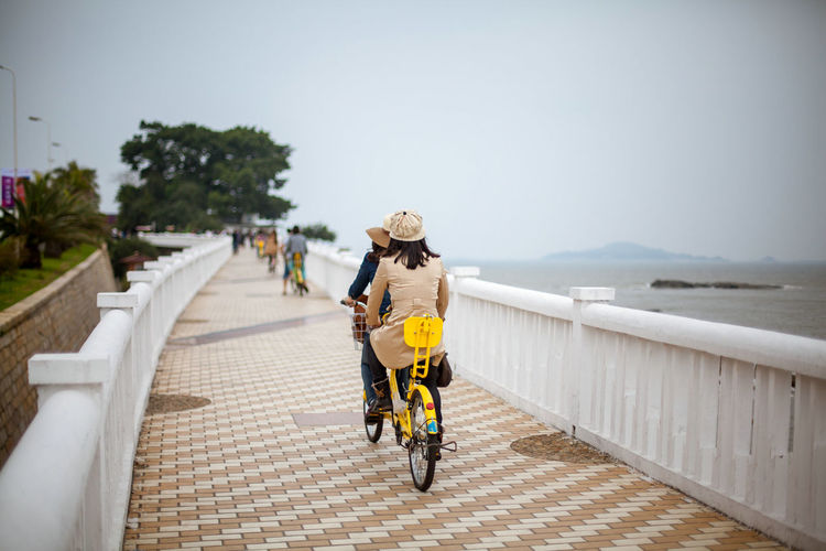 Women Riding Bicycle On Walkway