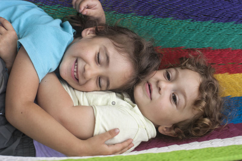 High Angle View Of Loving Siblings Lying On Textile