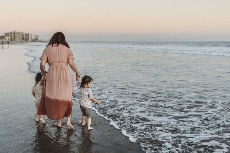 Rear view of mother and daughter by sea against sky