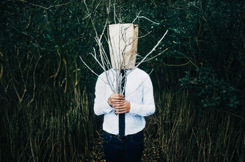Man in forest holding branches with paper covering face