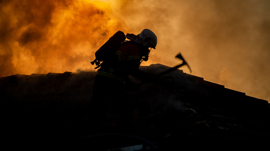 Side view of silhouette firefighter during sunset